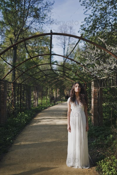 Beautiful pensive brunette woman in romantic white dress in the spring park.