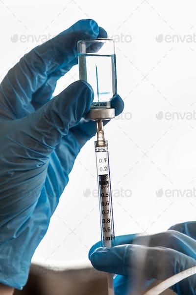 Doctor or Nurse Wearing Surgical Gloves Holding Vaccine Vial and Medical Syringe