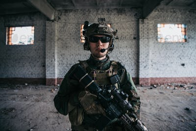 Military man with assault rifle standing inside building, he is ready for combat