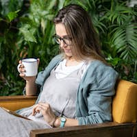 Woman gardener sitting on chair in green house resting using smartphone drinking tea. Home gardening