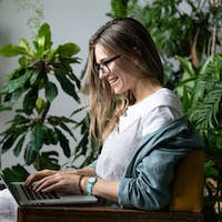 smiling woman freelancer sitting on chair in home garden, using laptop and talking in video chat.