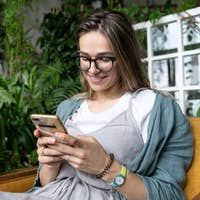 smiling freelancer woman sitting on chair in greenhouse resting surfing social networks on cellphone
