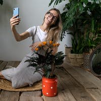 Happy woman gardener talking on video call on smartphone sitting near calathea plant in red milk can