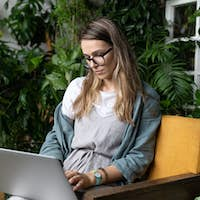 Young woman freelancer sitting on chair in green house, remote working on laptop in home garden.