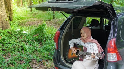 asian woman tavelling wearing hijab playing guitar with a car