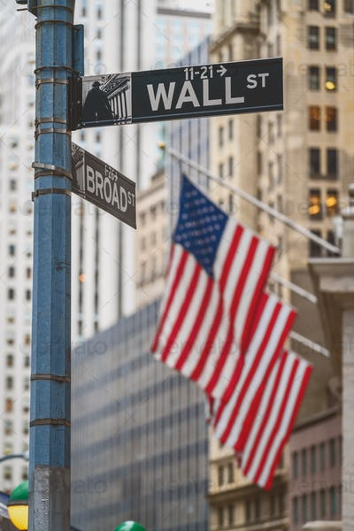 """Wall Street """"WALL ST"""" sign and broadway street over American national flags"""
