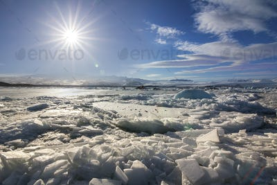 Ice on ice beach with sun and sun flare at noon, Iceland
