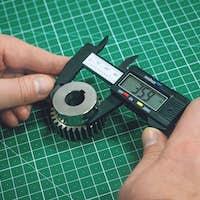 Metal gear measurement process. Factory man, worker measuring steel detail, gear with digital