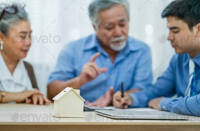 Closeup house mockup with laptop over the insurance agency manager signing contract with Asian