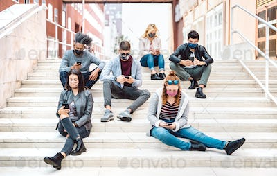 Urban milenial people using mobile phones covered by face masks