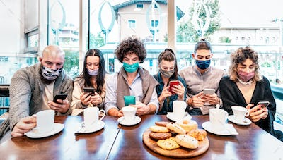 People using mobile smart phones at coffee bar covered by face masks