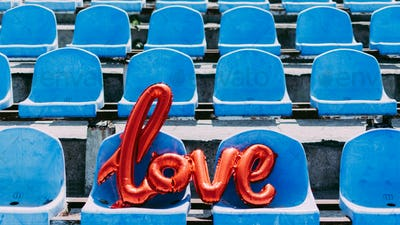 Love red foil balloon on blue stadium seats. Letter-shaped balloons forming the word love lifestyle