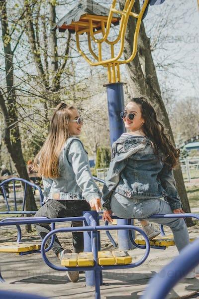Gen z girls enjoying outdoors, expressing positive emotions. Outdoor photo of two girl friends
