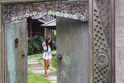 Young beautiful woman walking near old antique house in Bali style