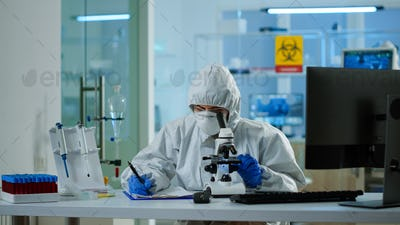 Biologist in ppe suit working on microscope and writing information on clipboard