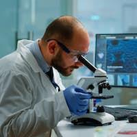 Male scientist looking under microscope in medical development laboratory