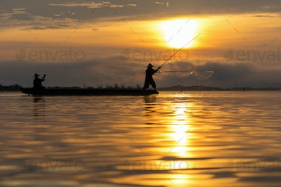 Silhouette of asia traditional fisherman in action when fishing at sunrise in the nature river
