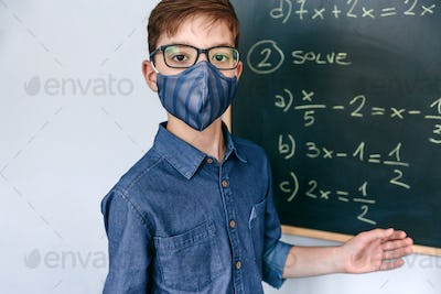 boy with mask in front of a blackboard with equations