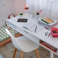 Desk in girl's bedroom decorated in pastel colors