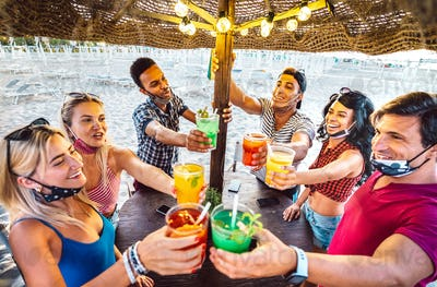 Young trendy friends toasting at beach cocktail bar chiringuito