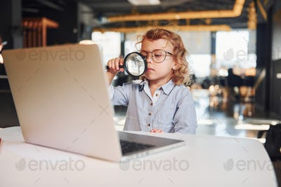 Smart child in casual clothes with laptop on table have fun with magnifying glass