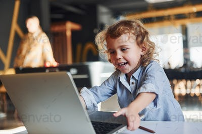 Smart child in casual clothes using laptop for education purposes or fun