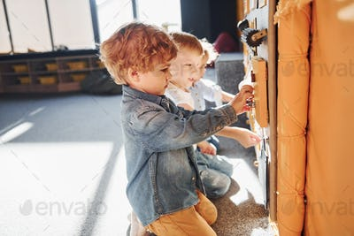 Children have fun in playroom near the wall. Kindergarten educational games