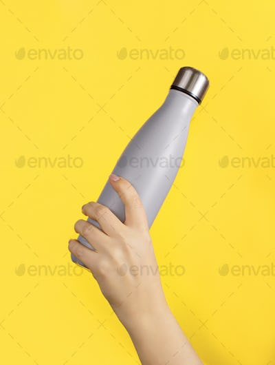 Hand with grey reusable insulated bottle on yellow background