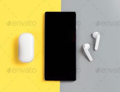 Smartphone and white wireless earphones