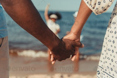 close-up partial view of african american couple holding hands while standing at seaside