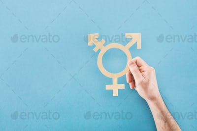 cropped view of male hand with white paper cut gender sign on blue background, lgbt concept