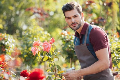 portrait of handsome gardener in apron holding disposable cup of coffee in garden