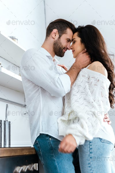 low angle view of lovely gently couple embracing at kitchen