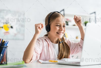 Selective focus of smiling child in headset showing yes gesture during online education at home