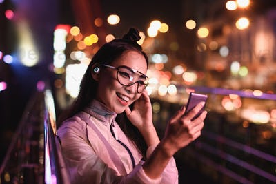 happy asian girl having video chat and using smartphone on street with neon light, city of future