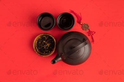 top view of oriental decoration and ceramic tea set isolated on red