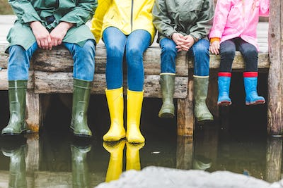 partial view of family in rubber boots sitting on wooden bridge near lake