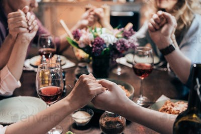 close-up partial view of people holding hands and praying before dinner