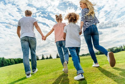 back view of happy family holding hands while walking together in park