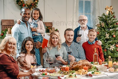 beautiful large family celebrating christmas with glasses of wine and looking at camera