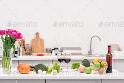 various vegetables with red wine and flowers on table at kitchen