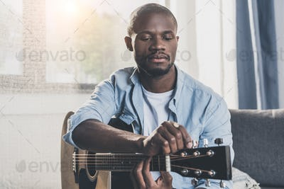 African american man tuning acoustic guitar at home