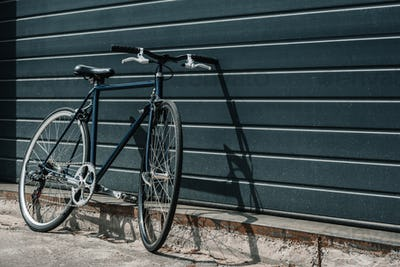 Black classic hipster bicycle standing near black wall outdoors