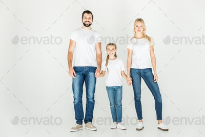 happy family with one child holding hands and smiling at camera isolated on white
