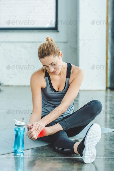 sportswoman with injured foot resting on mat in gym