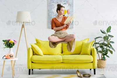 elegant young woman in lotus pose levitating in air while reading book in living room