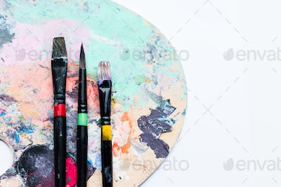 Artistic brushes on palette covered with colorful paint spots