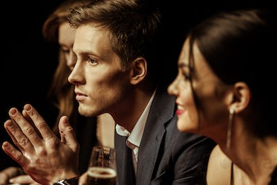 Side view of elegant young people drinking alcohol and looking away on black