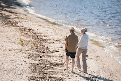 Back view of senior couple holding hands and walking on sand at riverside