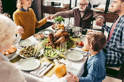 beautiful religious family holding hands and praying on thanksgiving before holiday dinner